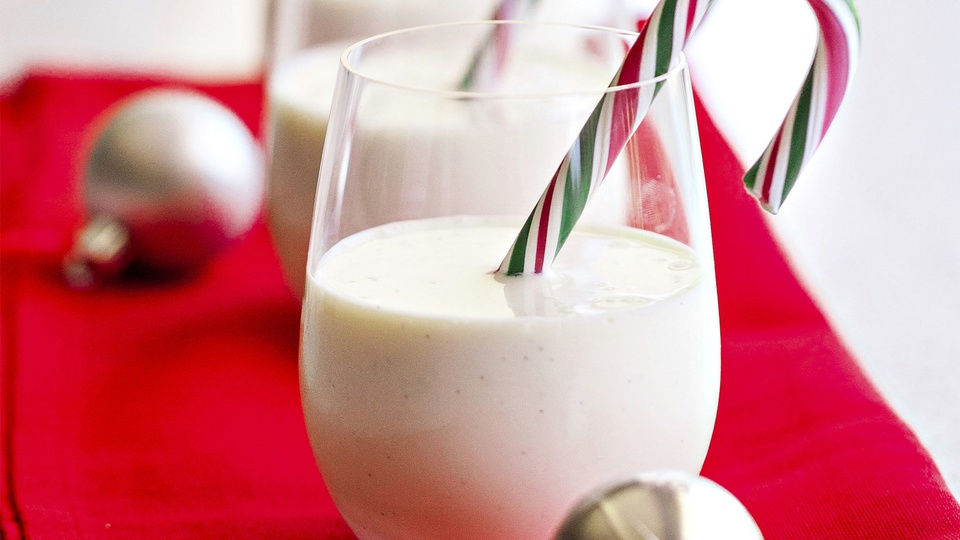 Glass of snow white cocnout peppermind egg nog with a candy cane stirrer