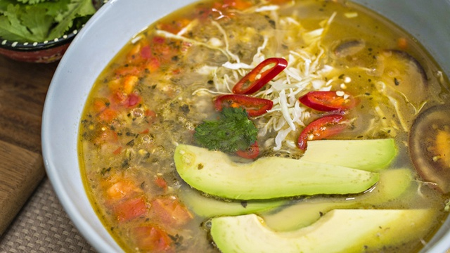 Bowl of brothy tortilla and chicken soup served with slices of avocado and chilli