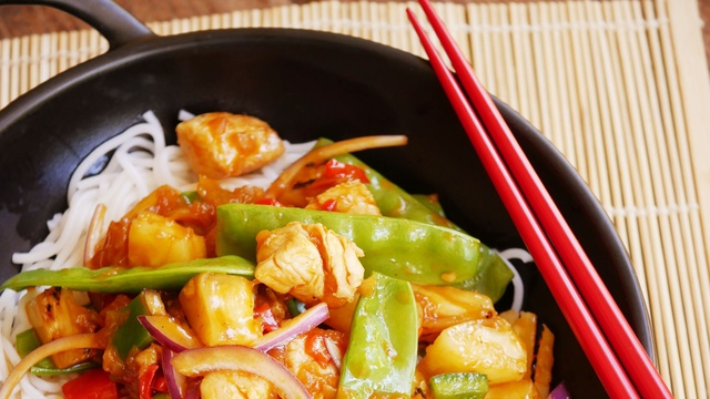 Chunks of moist chicken and mixed veg sit on top of fluffy white rice covered in bright orange sweet and sour sauce