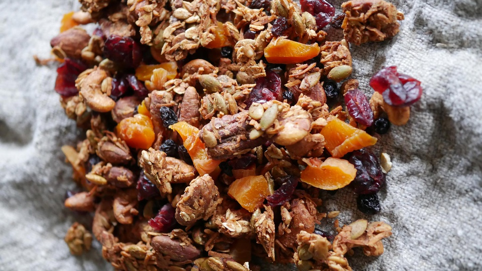 Brown trail mix with nuts seeds bright dried orange and deep red cranberries