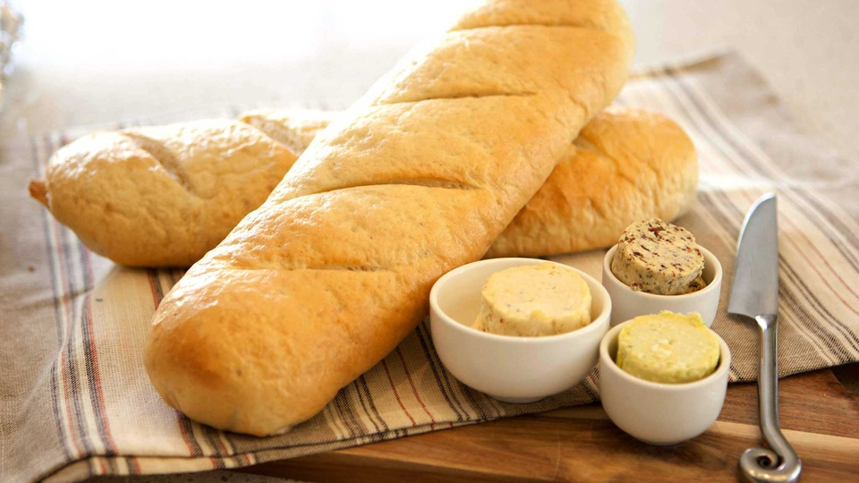 Two sticks of golden French baguettes served with three different herbed butters