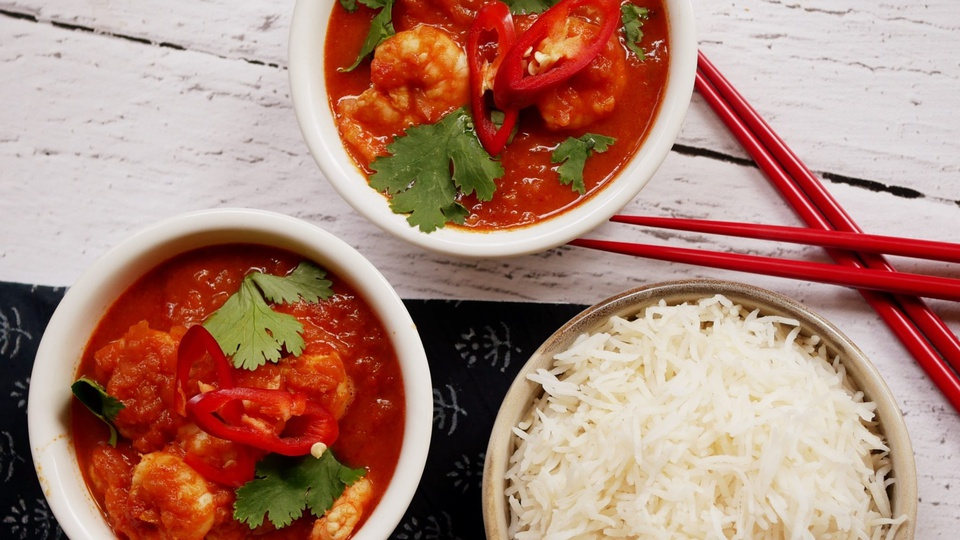 Vibrant red curry with prawns in bowls are set beside a cup of rice and matching chilli-red chopsticks