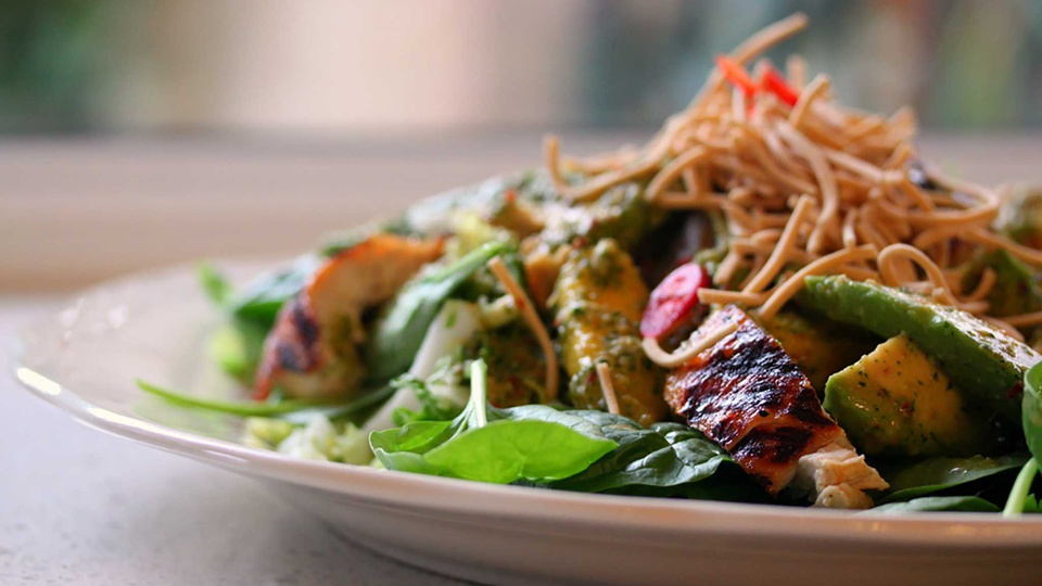 A side view of a leafy noodle salad with mango avocado and blackened chicken