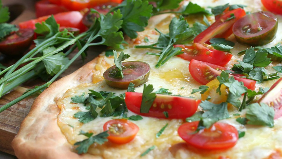Thin and crispy pizza base with melted cheese, ripe cherry tomatoes and parsley