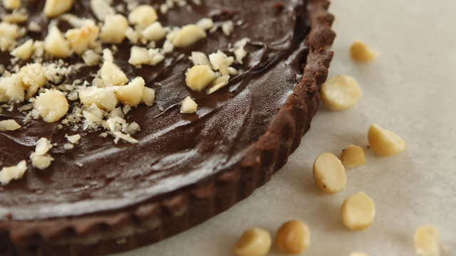 Deep brown chocolate tart filled with salted caramel chocolate ganache garnished with macadamia nuts